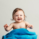 Baby girl sitting in a blue blanket, smiling - PhotoDune Item for Sale