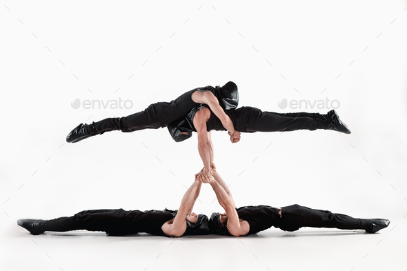The group of gymnastic acrobatic caucasian men on balance pose - Stock Photo - Images