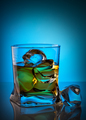 Whiskey in transparent glass with ice cube lying on glass table - PhotoDune Item for Sale