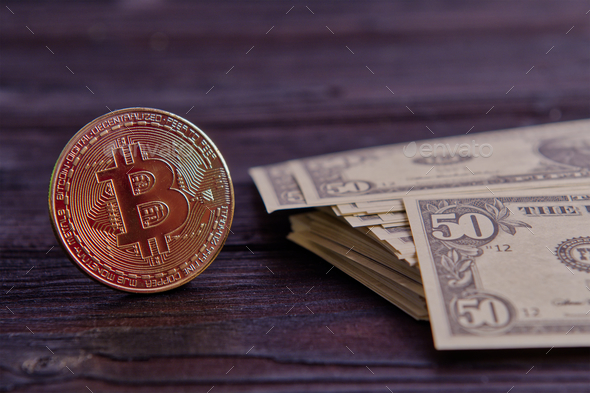 Dollar banknotes and Bitcoins on a wooden table - Stock Photo - Images