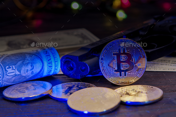 Bitcoins and dollar banknotes on a table with UV light - Stock Photo - Images