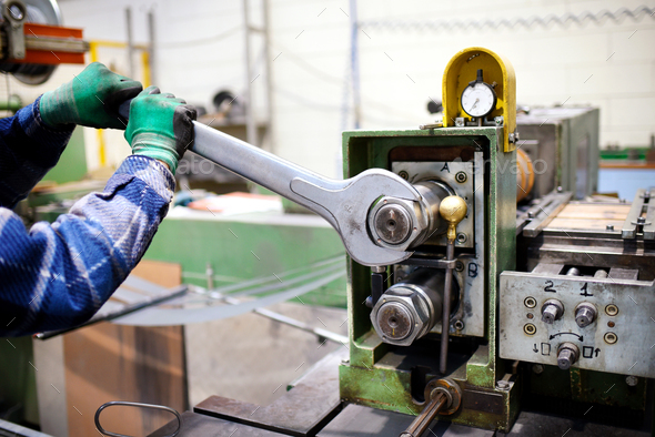 Worker adjusting machinery with large wrench - Stock Photo - Images