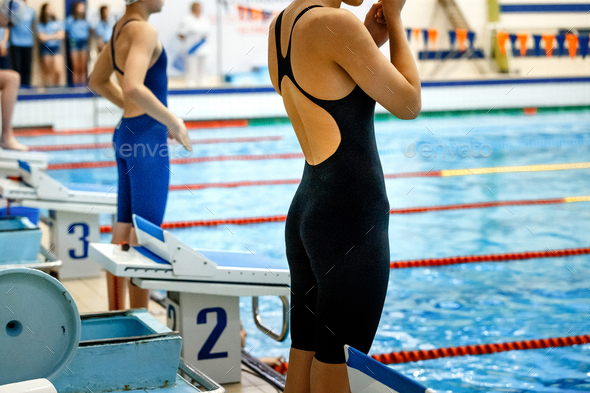 women athletes swimmers at start line - Stock Photo - Images