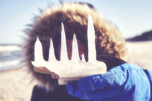 Close up picture of icicles held by a woman on a beach. - Stock Photo - Images