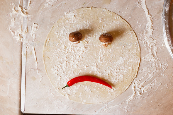 Dough basis for pizza in the shape of sad face - Stock Photo - Images