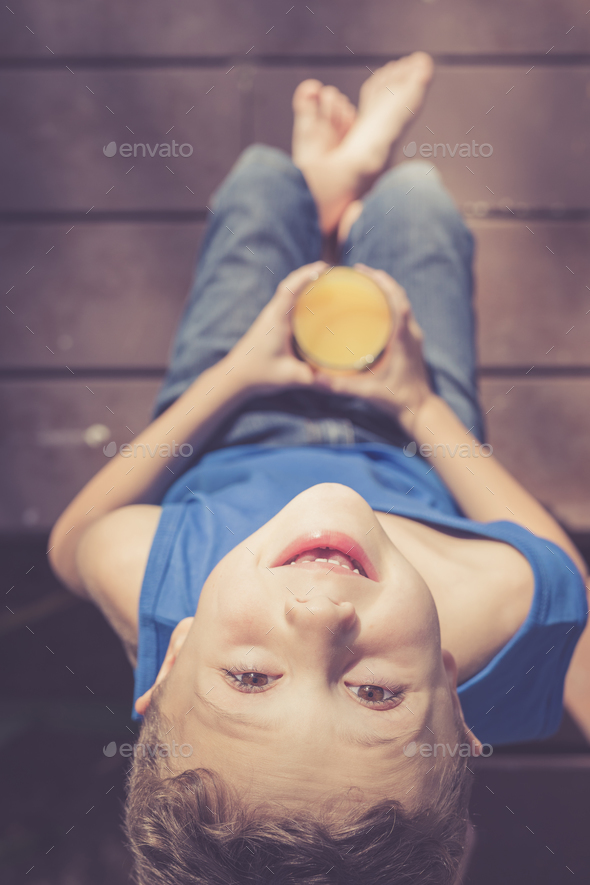 one boy is sitting with a glass of juice - Stock Photo - Images