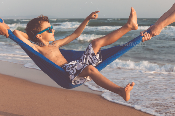 Happy little boy relaxing on the beach at the day time - Stock Photo - Images