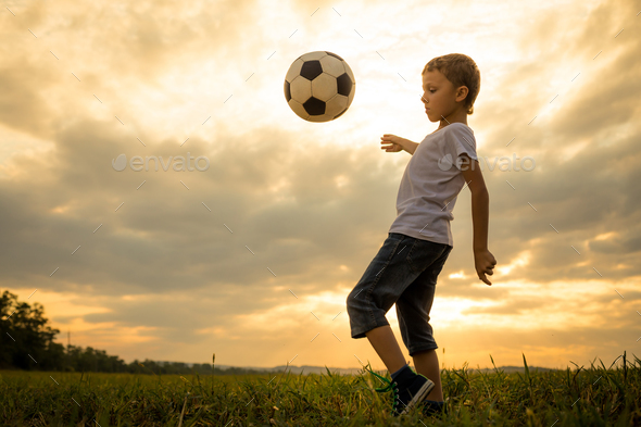 Young little boy playing in the field  with soccer ball. - Stock Photo - Images