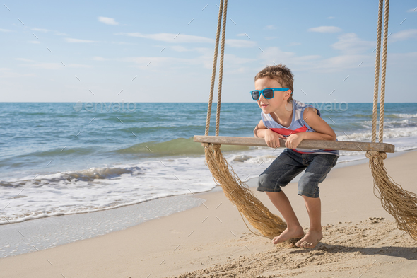 One happy little boy playing on the beach at the day time. - Stock Photo - Images
