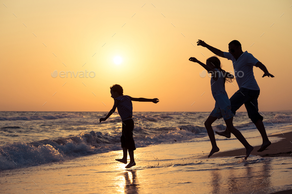 Father son and daughter playing on the beach at the sunset time. - Stock Photo - Images