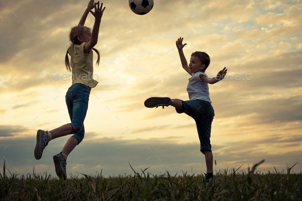 Happy young little boy and girl playing in the field  with socce - Stock Photo - Images