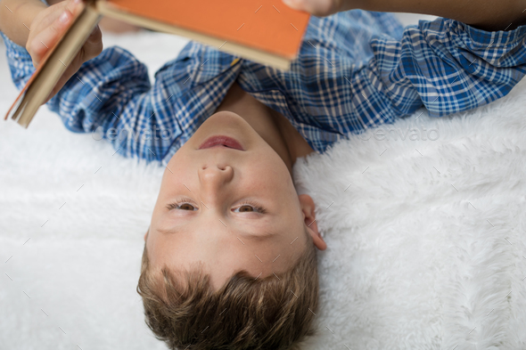 little boy is lying on the bed and reading a book - Stock Photo - Images