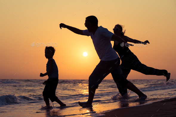 Father mother and  son  playing on the beach at the sunset time. - Stock Photo - Images