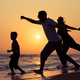 Father mother and  son  playing on the beach at the sunset time. - PhotoDune Item for Sale