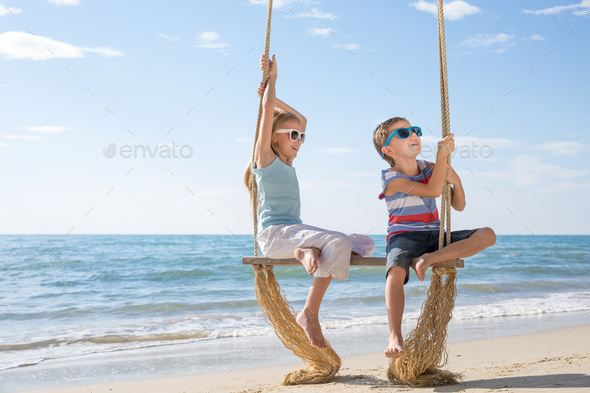 Two happy little children playing on the beach at the day time. - Stock Photo - Images