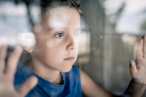 one sad little boy standing near the window at the day time. - Stock Photo - Images