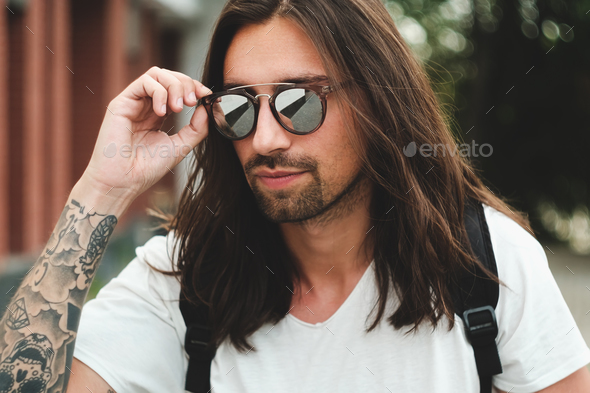 Portrait attractive man with sunglasses on urban background smil - Stock Photo - Images