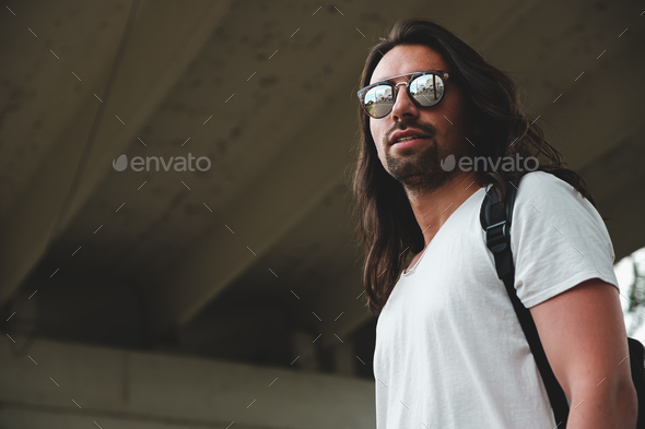 Model wearing fashionable sunglasses reflecting the city - Stock Photo - Images