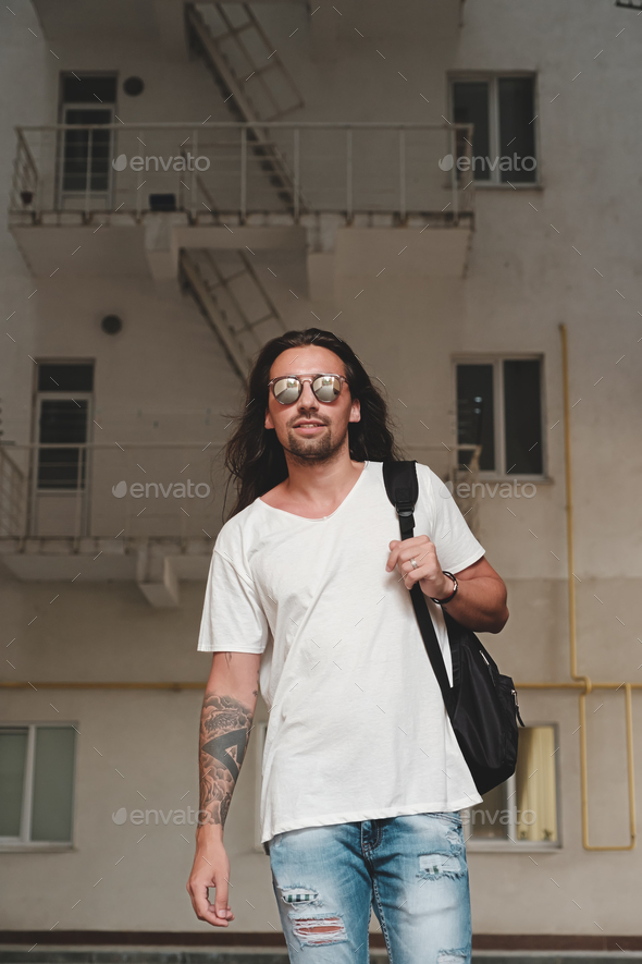 Man on urban background with backpack and sunglasses - Stock Photo - Images