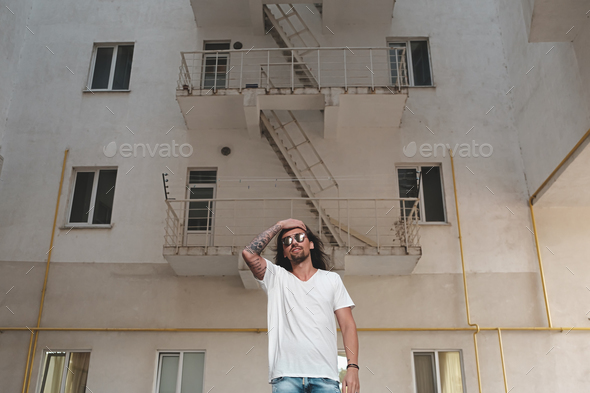 Stylish bearded man with long hair and tattoos posing - Stock Photo - Images