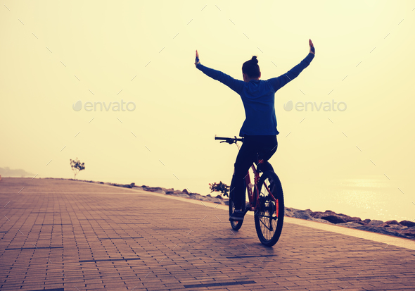 free woman cyclist outstretched arms on sunrise seaside - Stock Photo - Images
