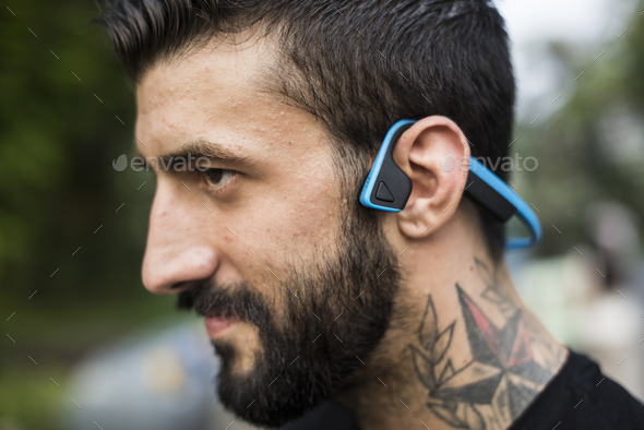 A man with bluetooth headphones - Stock Photo - Images