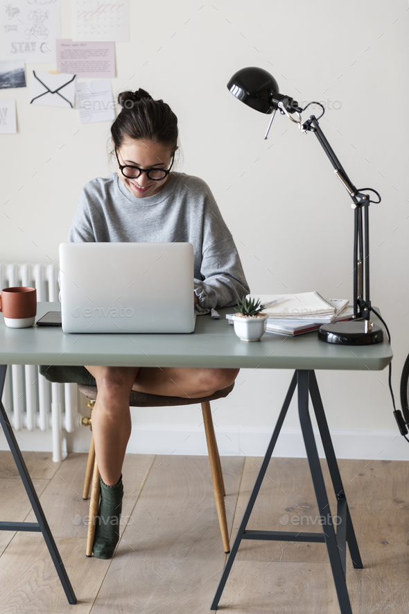 Woman working on a laptop in her home - Stock Photo - Images