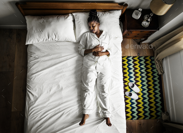 African American woman on bed sleeping alone - Stock Photo - Images
