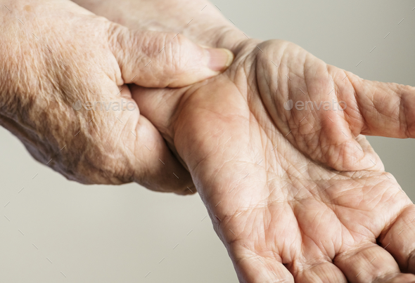 Closeup of elderly hands checking pulse - Stock Photo - Images