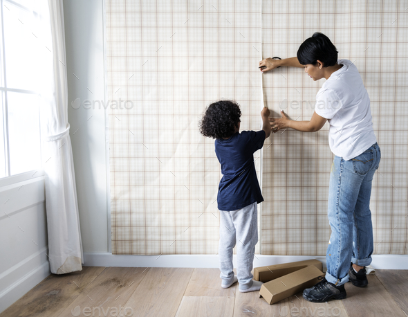 Kid helping mom install wallpaper - Stock Photo - Images