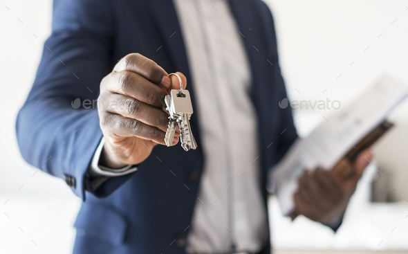 Real estate agent handing the house key - Stock Photo - Images
