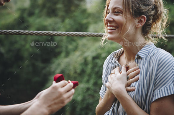 Man proposing to his woman with a red box - Stock Photo - Images