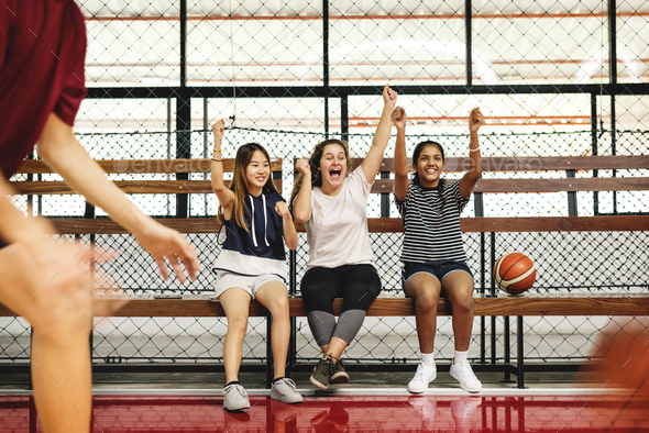 Teenage girls cheering the boys playing basketball - Stock Photo - Images