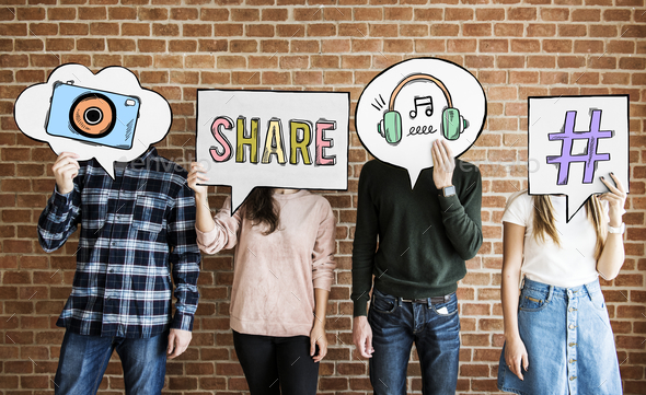 Friends holding up thought bubbles with social media concept ico - Stock Photo - Images