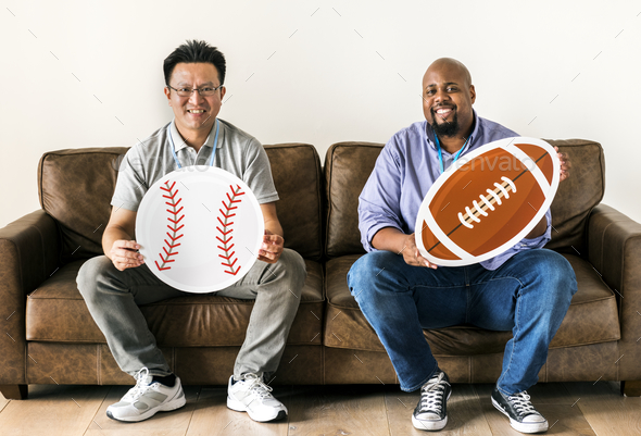 Men holding baseball and rugby icons sitting on couch - Stock Photo - Images