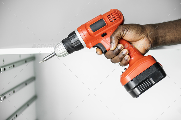 Man using electronic drill install cabinet - Stock Photo - Images