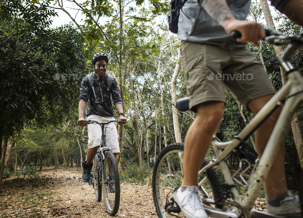 Group of friends ride mountain bike in the forest together - Stock Photo - Images