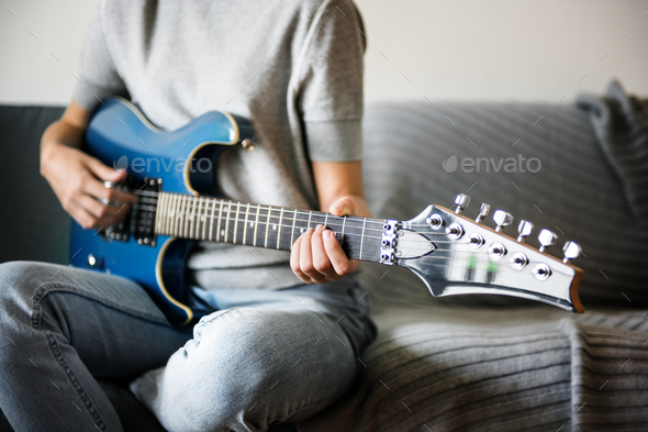 Woman playing an electric guitar - Stock Photo - Images