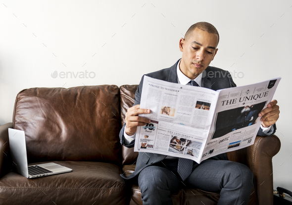Businessman reading newspaper and having coffee - Stock Photo - Images