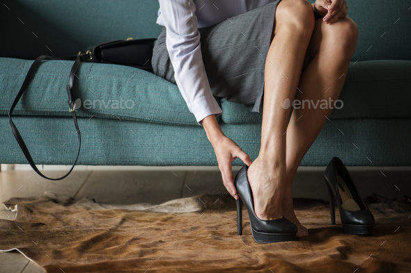 Woman taking off her high heels - Stock Photo - Images