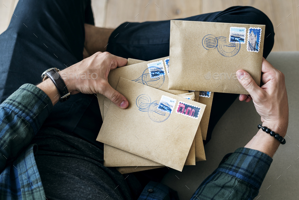 Aerial view of a man sorting an envelope - Stock Photo - Images