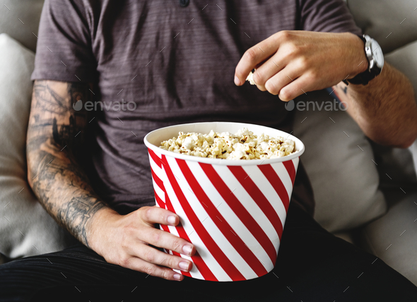 Man eating popcorn - Stock Photo - Images