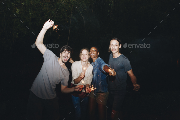 Friends having fun with sparklers in the night - Stock Photo - Images