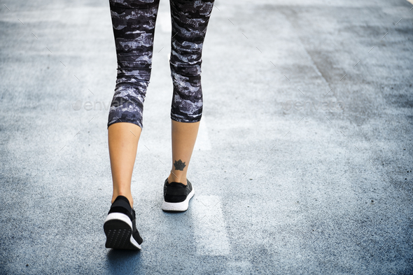 Woman jogging down the road - Stock Photo - Images