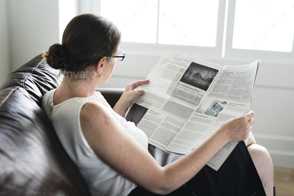 Businesswoman reading a newspaper on a couch - Stock Photo - Images
