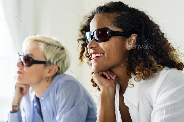 Young women watching three dimensional movie - Stock Photo - Images