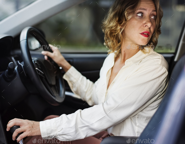 Woman driving a car in reverse - Stock Photo - Images