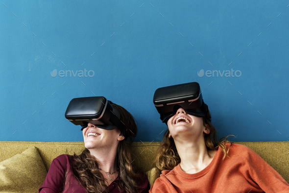 Two caucasian woman using VR on a sofa - Stock Photo - Images