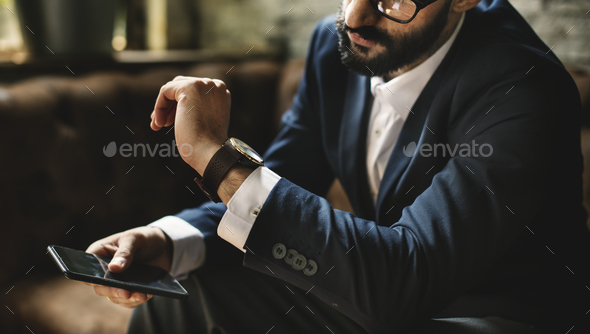 A businessman looking at a watch - Stock Photo - Images