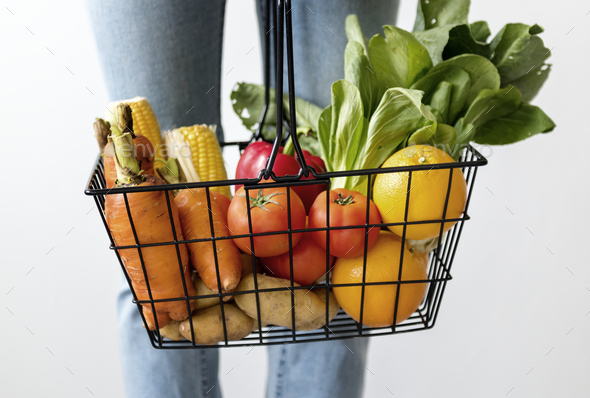 Woman holding vegetable basket - Stock Photo - Images